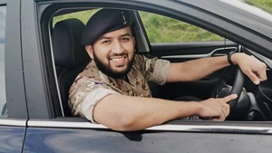 Signaller Lance Corporal Nile Janjua smiling in his car. He works in Stafford-based 22 Signal Regiment.