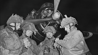 © IWM (H 39070) The Final Embarkation Four stick commanders of 22nd Independent Parachute Company British 6th Airborne Division synchronising their watches .png