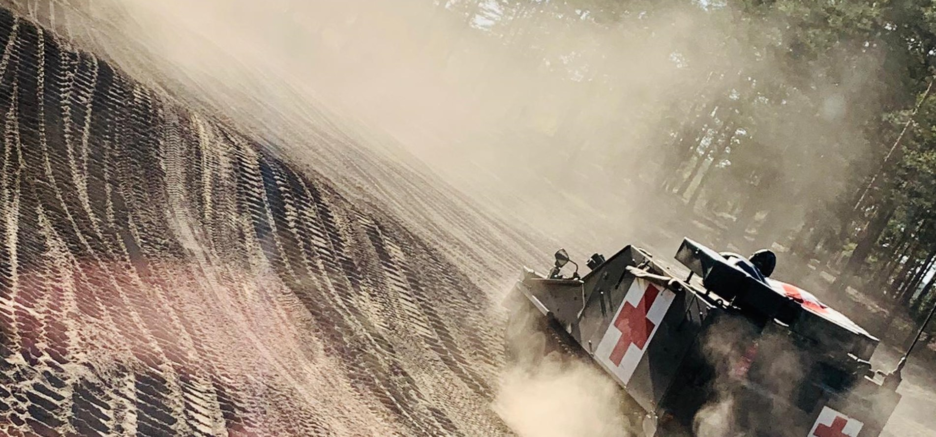 Kicking up dust - a Samaritan in support of Ex Arrow 19 follows D Sqn as they move through the woods!.JPG